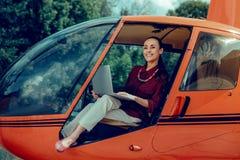 轻的休息在直升机的裤子和红色衬衣的刚毅快乐的夫人 图库摄影