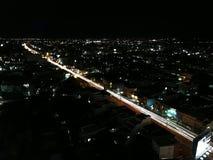 轻的城市夜,它很美丽在背景 免版税库存照片