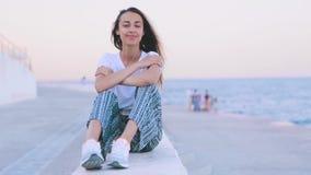 轻的夏天衣裳的美丽的年轻女人坐码头在港口在黎明 年轻白种人女性观看 股票视频