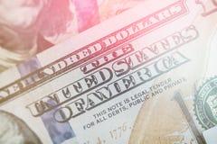 轻的定调子的宏指令接近本富兰克林在美国100美金的` s面孔 库存图片