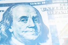 轻的定调子的宏指令接近本富兰克林在美国100美金的` s面孔 库存照片