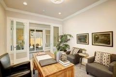 轻的家庭办公室以一张木书桌为特色 免版税图库摄影