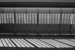 轻的影子 黑色白色 从金属格子的晴天光在被放弃的未完成的shoping的购物中心 库存图片