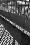 轻的影子 黑色白色 从金属格子的晴天光在被放弃的未完成的shoping的购物中心 库存照片