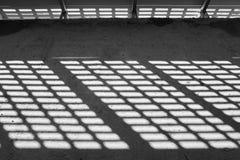 轻的影子 黑色白色 从金属格子的晴天光在被放弃的未完成的shoping的购物中心 免版税库存图片