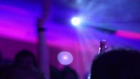 轻的火光和拍的手在天空中在夜总会在迪斯科聚会期间 股票录像