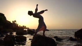 轻的礼服跳舞的可爱的白种人深色的女孩在岩石在日出时间的海 股票视频