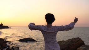 轻的礼服跳舞的可爱的白种人深色的女孩在海上的峭壁日出时间的 股票录像