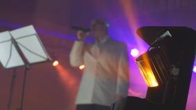 轻的聚光灯音乐会减速火箭的音乐会被弄脏的背景生活方式 资深唱歌入话筒的一个老人 股票录像