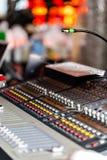 轻的设备操作员混合的控制台音乐会的 有工程师或音乐的录音演播室混合的书桌 免版税库存图片