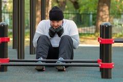 轻的运动服、帽子和防护手套的一个年轻人在他的做腹肌的发展的手上锻炼 免版税库存照片