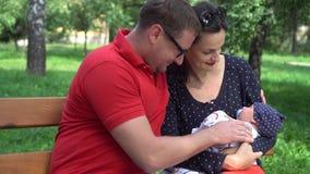 轻轻地拿着他们美丽的新生儿男孩的爱的年轻白种人父母 影视素材