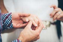 轻轻地拿着在他的新娘手上的新郎一只金戒指 免版税库存图片