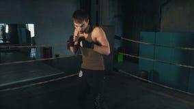 轻量级拳击手拳打在圆环的照相机在葡萄酒健身房 股票录像
