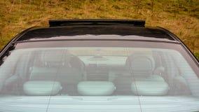 轿车在看法里面的运动器材汽车通过后方挡风玻璃、皮革内部,被镀铬的元素,前面和后座 库存图片