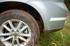 轿车的多灰尘的spoked轮子在草停放了 免版税库存照片