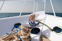 辅助工一点 男孩可爱的水手镶边衬衣游艇旅行在世界范围内 与绳索的儿童逗人喜爱的水手帮助乘快艇弓 免版税库存图片