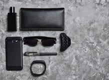 辅助部件和小配件一个女商人的凝结面上 智能手机,巧妙的镯子,笔,香水瓶,钱包 免版税库存图片
