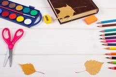 辅助部件,书和秋季叶子框架学会和教的在委员会,回到学校概念 库存照片