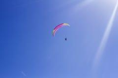 辅导员和初学者的一前一后一个滑翔伞的在明亮的蓝天 库存图片