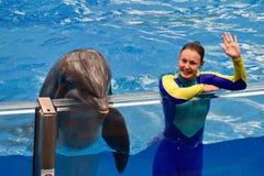 辅导员女孩挥动的手问候和好的海豚 免版税库存照片