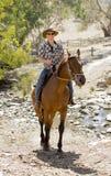 辅导员或牧畜者在太阳镜、牛仔帽和车手起动的骑乘马 免版税库存照片