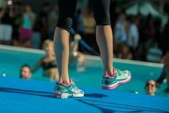 辅导员腿特写镜头在游泳池边缘的:水色有氧运动锻炼 库存图片