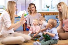 辅导者和1岁婴孩在幼儿园或托儿所使用与教育玩具 免版税库存图片