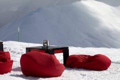 辎重袋椅子和桌在室外咖啡馆在滑雪胜地 免版税库存图片