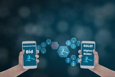 输入出价的价格的女性手藏品智能手机,通过在蓝色bokeh背景的无线网络与拍卖象,概念 免版税库存图片