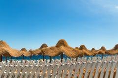 输入在海滩的海滩睡椅和伞棍打 免版税库存照片