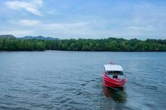 输入在Pakbara口岸的一艘红色船在蓝天和蓝色海下 免版税库存照片