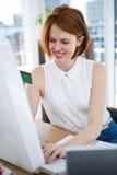 输入她的信用卡细节的微笑的行家女商人 库存照片