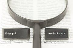 输入并且前退计算机键盘和一个透镜在书页 库存图片