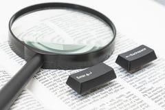 输入并且前退计算机键盘和一个透镜在书页 库存照片