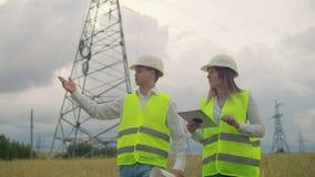 输电线、人和妇女工程师有一种片剂的在他们的手上检查新的塔的设施的进展 股票视频