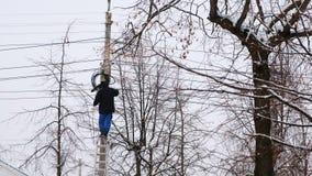 输电线人修理在城市在冬天 在一架梯子的立场与一根导线在他的手上,后面视图 影视素材