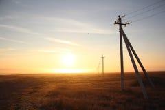 输电线在薄雾的黎明 免版税库存图片