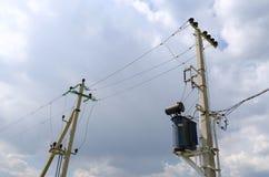 输电线支持的柱子在农村地点 免版税库存照片