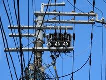 输电线绝缘体、连接器和被缠结的导线在一根电子杆 免版税图库摄影