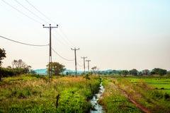 输电线通过农田 免版税库存图片