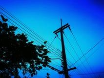 输电线,电话在同一根杆安装的传输导线剪影  免版税库存图片