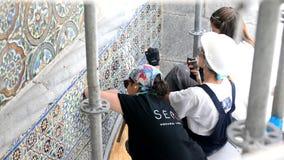 辛特拉,宫殿贝纳,葡萄牙- 2017年8月08日:妇女修理与凿子和锤子的老瓦片azulejos在P宫殿墙壁上  股票录像