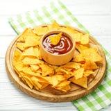辣墨西哥烤干酪辣味玉米片在一个木盘子切削 与ch的辣调味汁 免版税库存图片