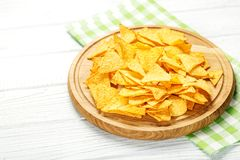 辣墨西哥烤干酪辣味玉米片在一个木盘子切削 概念-坏食物, 免版税图库摄影