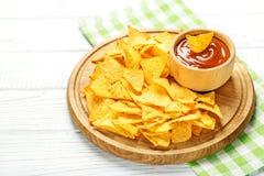 辣墨西哥烤干酪辣味玉米片在一个木盘子切削 自创西红柿酱 平面 库存照片