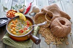 辣扁豆汤用辣椒、大蒜和葱在木桌上 免版税库存照片