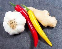 辣椒、大蒜和姜在黑背景 免版税库存照片