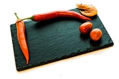 辣椒、蕃茄和一只虾在板岩板材,任意 免版税库存照片