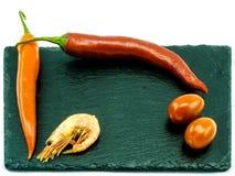辣椒、蕃茄和一只虾在板岩镀,隔绝 免版税库存照片